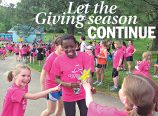 At the finish line of a Girls on the Run practice 5k, participants are handed a celebratory wand. (McKenzie Miller)