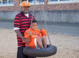 James Jones and his 6-year-old son, Laronzo, try out the tire swing behind King School. They returned to live in King because they believe it's a good neighborhood and has good schools. (Judy Nelson)