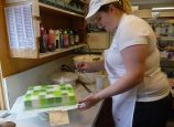 """Decorator Joy Childress sprays green frosting on a cake for a boy who loves the Minecraft online game. Girls who like the film """"Frozen"""" request cakes shaped like skirts around Elsa dolls. Besides birthday cakes, Helen Bernhard Bakery fills about 300 orders a year for wedding cakes. (Janet Goetze)"""