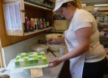 "Decorator Joy Childress sprays green frosting on a cake for a boy who loves the Minecraft online game. Girls who like the film ""Frozen"" request cakes shaped like skirts around Elsa dolls. Besides birthday cakes, Helen Bernhard Bakery fills about 300 orders a year for wedding cakes. (Janet Goetze)"