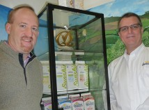 Dirk Davis, left, CEO of Sunshine Dairy Foods, and Rob Johnson, director of revenue operations, show the cartons with a new logo, on the second shelf, and cartons for other products produced by the 80-year-old business. Changing consumer tastes are sending the dairy processor in new directions. (Janet Goetze)