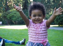 A friendly 18-month-old girl named Meklit, welcomes visitors to Laurelhurst Park on a sunny Sunday afternoon. She joined her father and friend who live in Northeast Portland, for a concert in the Park.